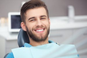a young man smiling in the dentist chair