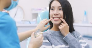A dentist pointing at a female patient's smile.