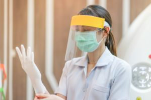 Greensboro dentist dons PPE in preparation for dental appointment