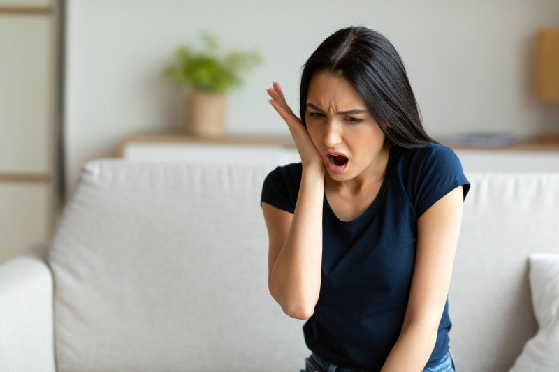 A woman seated on a couch and holding her jaw while cringing in pain