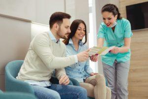 dental team member explaining dental insurance to two patients